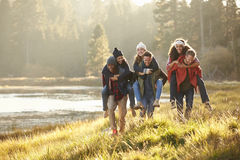 Six friends have fun piggybacking in the countryside by lake Stock Photos