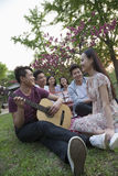 Six friends having a picnic and hanging out in the park, playing guitar and talking Stock Photography