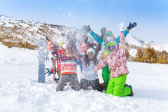 Six friends with snowboards and skis throwing snow Royalty Free Stock Photo