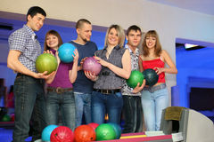 Six friends stand and holds balls for bowling stock photo