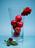 Six fruits in glass vase and roses on blue Royalty Free Stock Images