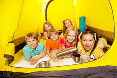 Six funny children laying in the tent. Six funny children laying in the yellow camping tent with thermos and aluminum cups Stock Photos