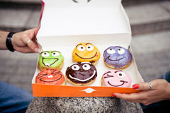 Six funny donuts in a box. Six funny donuts with different emotions in a box Stock Photo