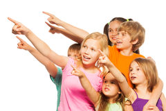 Six funny kids point fingers aside. Photo of a six funny kids in colorful shirts pointing fingers stock photography