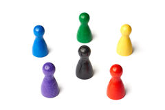 Six game figures standing in a circle with a black figure in the middle. Symbol for a color wheel or a group of people Stock Photo