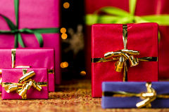 Six Gifts with Bow Knots. Christmas presents in plain colors placed on a festive cloth. Seasonal background with plenty of text space. Shallow depth of field Stock Image