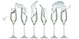 Six glasses with splashes of champagne isolated Stock Photos