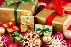 Six Golden Xmas Presents with Bows. Six Christmas gifts all wrapped in gold. Bows in red and green also. Placed next to straw stars and ornaments on a red cloth Stock Image