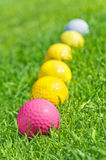 Six golf balls on the green grass Royalty Free Stock Photo