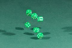 Six green dices falling on a green table. Six green dices falling on a isolated green table royalty free stock photos