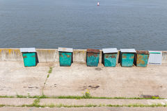 Six (6) green garbage containers standing on the stone embankmen Royalty Free Stock Photos