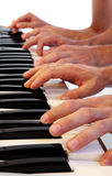 Six hands on grand piano Stock Photos