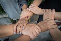 Six hands of multiracial colleague holding wrists of each other hands as team, business teamwork concept. Six hands of multiracial colleague holding wrists of Stock Images
