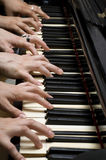 Six hands on piano Stock Images
