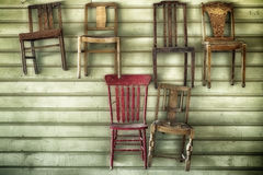 Six Hanging Wood Chairs. Six wooden chairs hanging from a wood sided wall inside a party hall. One of the chairs is painted red. Photographed on the back roads Stock Photos