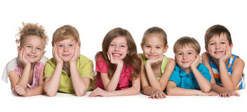Six happy children. Group of six joyful children are lying on the floor on a white background Stock Image