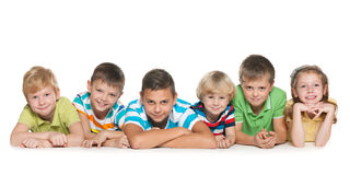 Six happy children. Are lying on the floor on a white background Stock Image