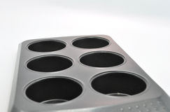 Six holed muffing baking tray. Muffin baking tray set against a light blue background Royalty Free Stock Photography