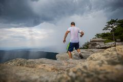 Man Running across McAfee Knob while raining in the valley stock photos