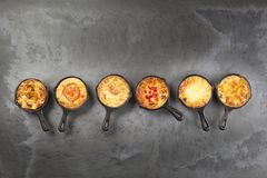 Six quiches in frying pans. Six individual mini quiche pies in cast iron pans on a dark slate effect surface stock photography