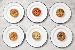 Six quiche pies on plates. Six individual mini quiches on white enamel plates on a light coloured table top stock image