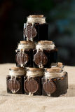 Six ink bottles, mummy,  in jars with wax. Standing pyramid on sacking and darck blue background Royalty Free Stock Photo