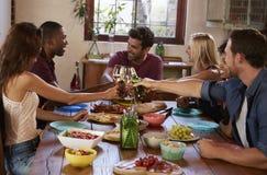 Six jeunes amis adultes faisant un pain grillé à un dîner Photos stock