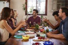 Six jeunes amis adultes s'asseyant à la table pour un dîner Photos libres de droits
