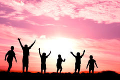 Six jumping childen silhouette. Six children jumping for joy silhouetted sunset Stock Photo