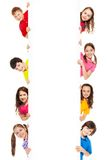 Six kids looking from blank billboard. Six kids, boys and girls showing blank white board for advertising to be inserted, isolated on white Royalty Free Stock Photography