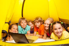 Six kids lay in a yellow tent. Six smiling kids lay in a yellow tent with a laptop watching images and smiling Royalty Free Stock Photos