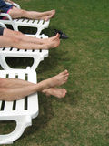 Six legs. Three sets of legs lounging in lounge chairs on grass near lake Stock Photos