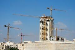 Six lifting cranes at construction site Stock Photos