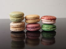 Six colourful macaron cookies, black reflective surface Stock Images