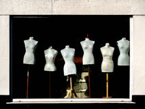 Window display of female mannequins on wooden stands Royalty Free Stock Photos