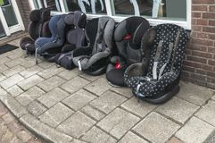 Six maxi-cosy baby seats standing outside royalty free stock photo