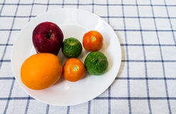 Six Mixed Fruits and Vegetables with Kaffir Lime on White Plate. Six Mixed Fruits and Vegetable with Kaffir Lime on White Plate Placed on Squared Background Royalty Free Stock Images
