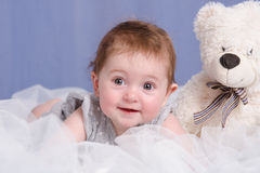 Six-month baby girl with teddy bear on sofa. Six-month beautiful charming girl on the couch stock image