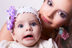 Six-month daughter with her mother surprised. 6 months baby girl surprised with a flower on her head, wearing a white blouse and a white ribbon on his head, in royalty free stock photo