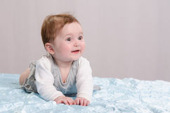 Six-month girl on the couch. Six-month beautiful charming girl on the couch stock photography