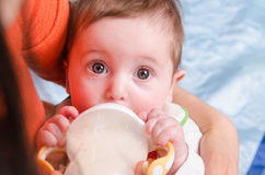 Six-month girl drinks milk from a bottle. Six month old baby drinking milk from a bottle with a nipple, lying on his mother's arms stock photography