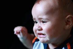Six month old baby crying. Portrait of a six month old baby who is so sad and crying. He is multicultural: caucasian and asian. He has adorable pouty lips Stock Image