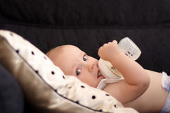 A six month old baby drinking out of his bottle Stock Image