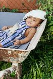 Six month old baby fun concept lying on wheel barrel as if tired from working too hard. Chilling out. royalty free stock photo