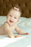 Six month smiling baby girl laying on the bed Stock Photos