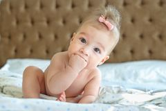 Six months baby girl sitting on the bed. Six months baby sitting on the bed fingers in her mouth Stock Photography