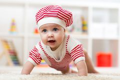 Six months old baby girl crawling on floor in nursery Royalty Free Stock Photo