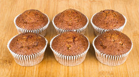 Six muffins in row on wooden board Royalty Free Stock Photography