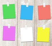 Six multi-colored paper notes on wooden surface. Royalty Free Stock Photo