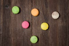 Six multicolored macarons on a brown wooden table. Top view.  Royalty Free Stock Photos